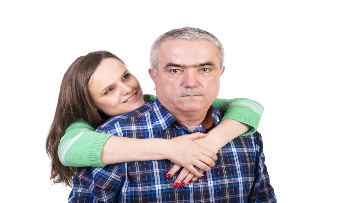 Portrait of happy daughter hugging her father against white background