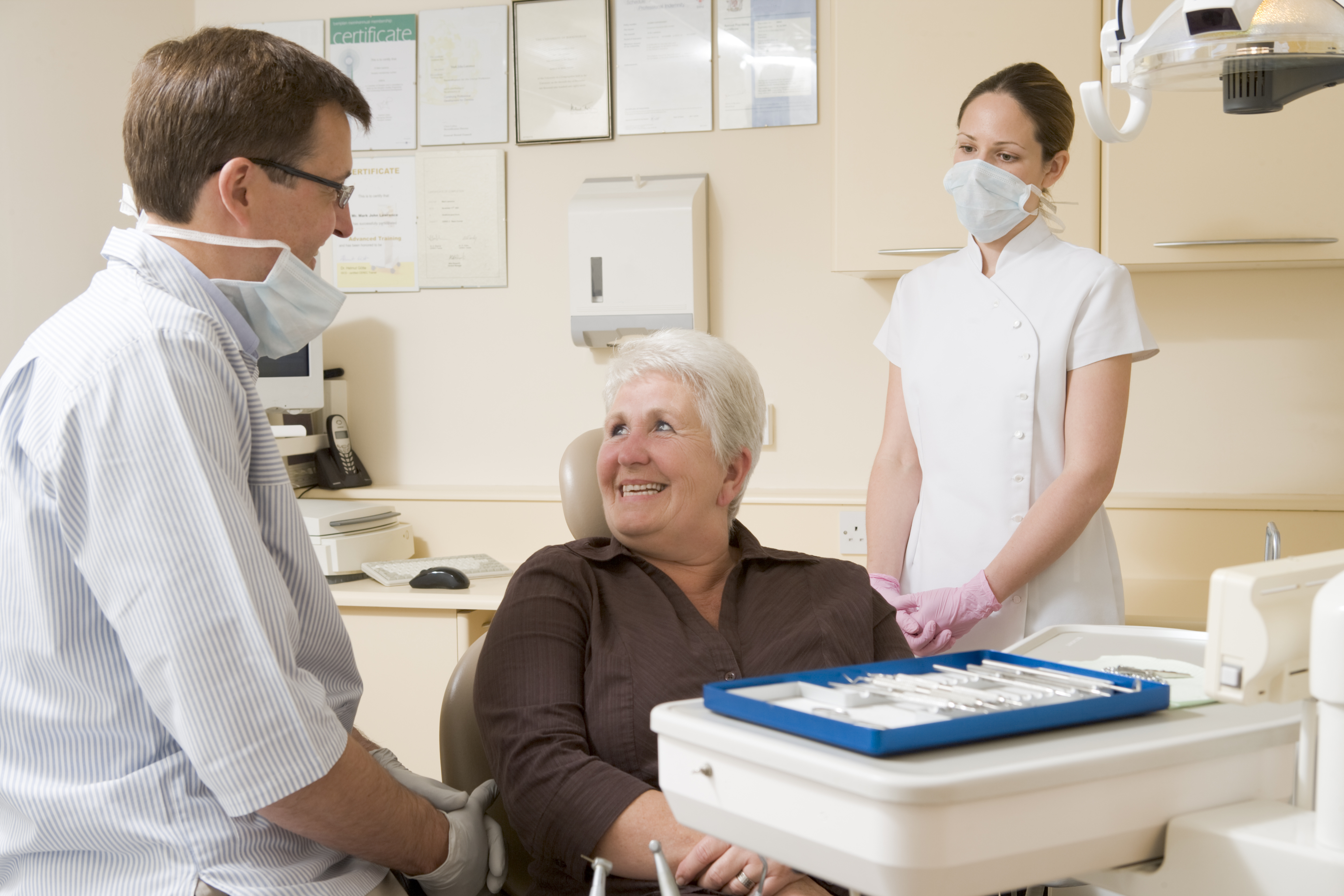 Dentist and assistant in exam room with woman