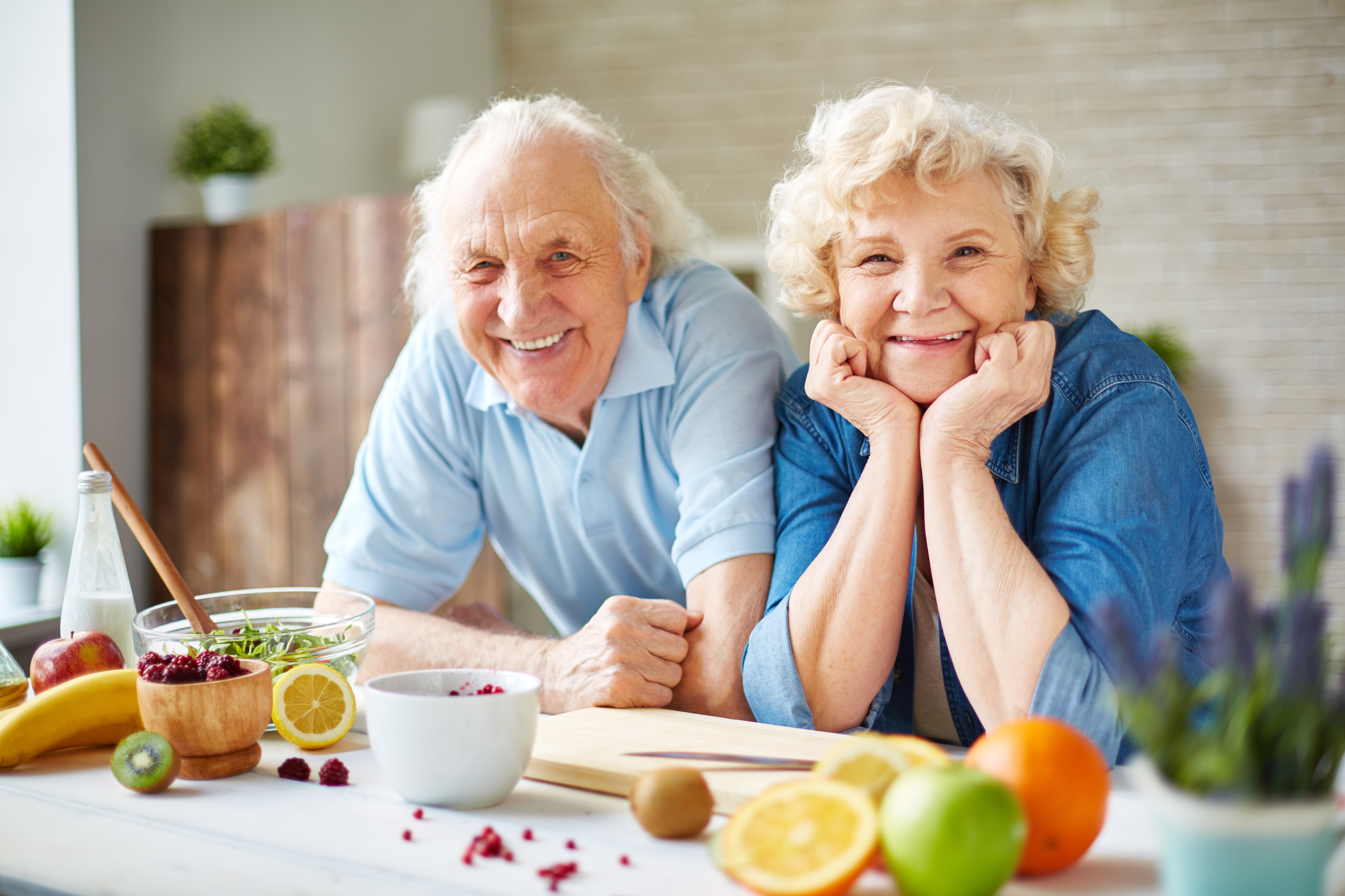 Happy senior man and woman looking at camera in the kitchen