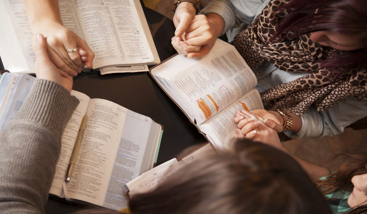 A group of young women bow their heads and pray with bibles.