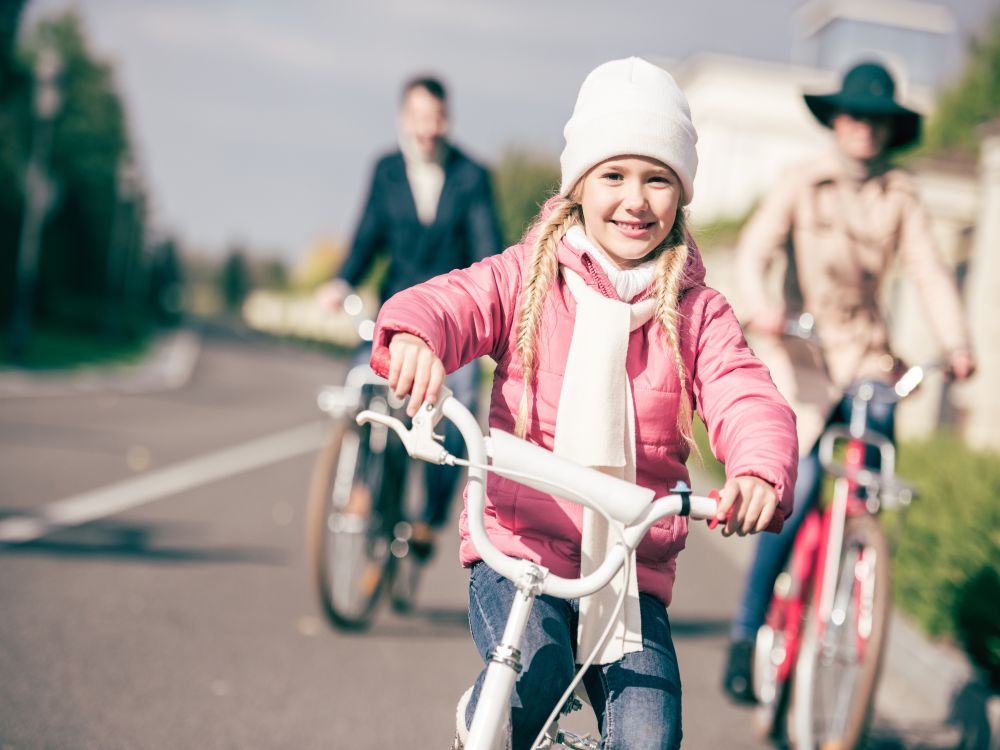 Close-up portrait of cute little girl riding bicycle with blurred parents on background